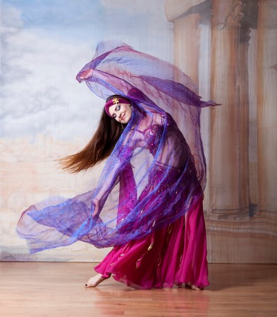 Belly dancer dancing with hair and scarf flowing in the air
