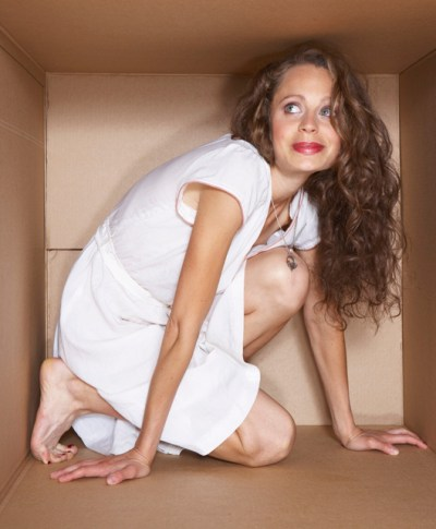 Young woman hiding in a box