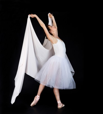 Ballet dancer in white tutu and pointe shoes with scarf