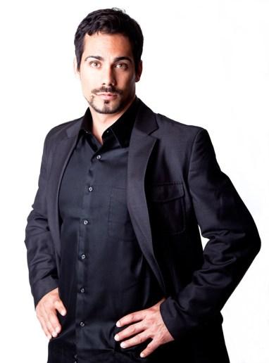 Handsome man dressed in black hands akimbo