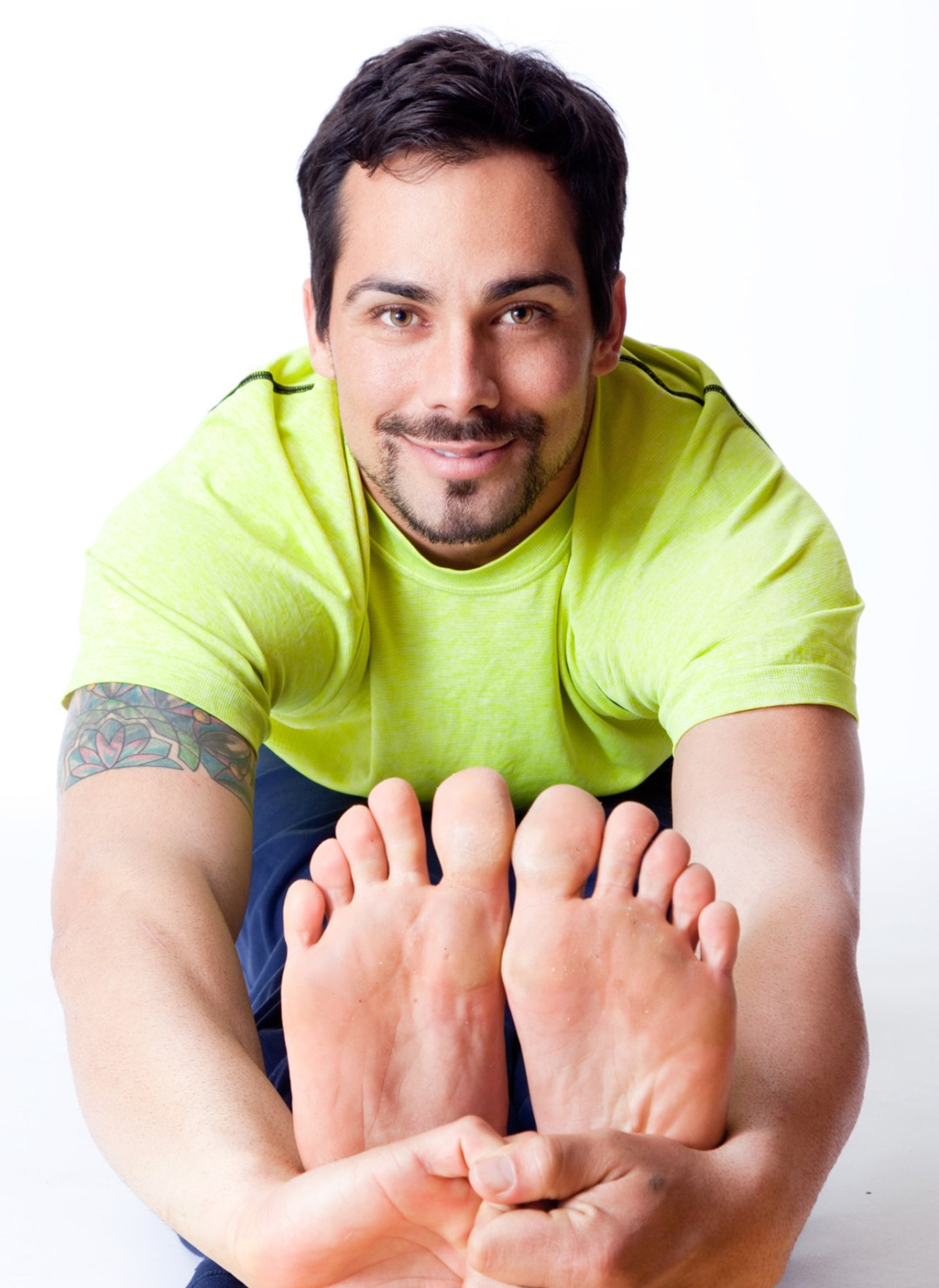 Male yogi with hands around his feet