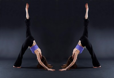 Mirror image of female dancer lifting her leg
