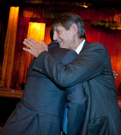 Peter Coyote hugging someone at fundraiser