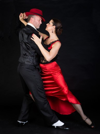 couple doing tango on black background