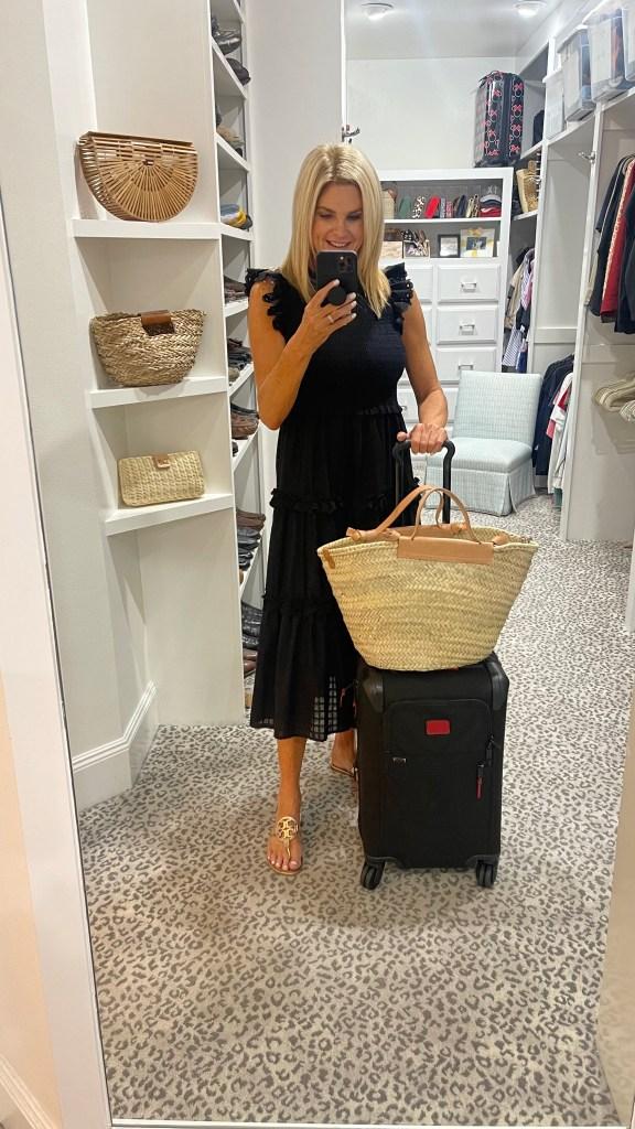 tanya foster wearing black avara midi dress with luggage