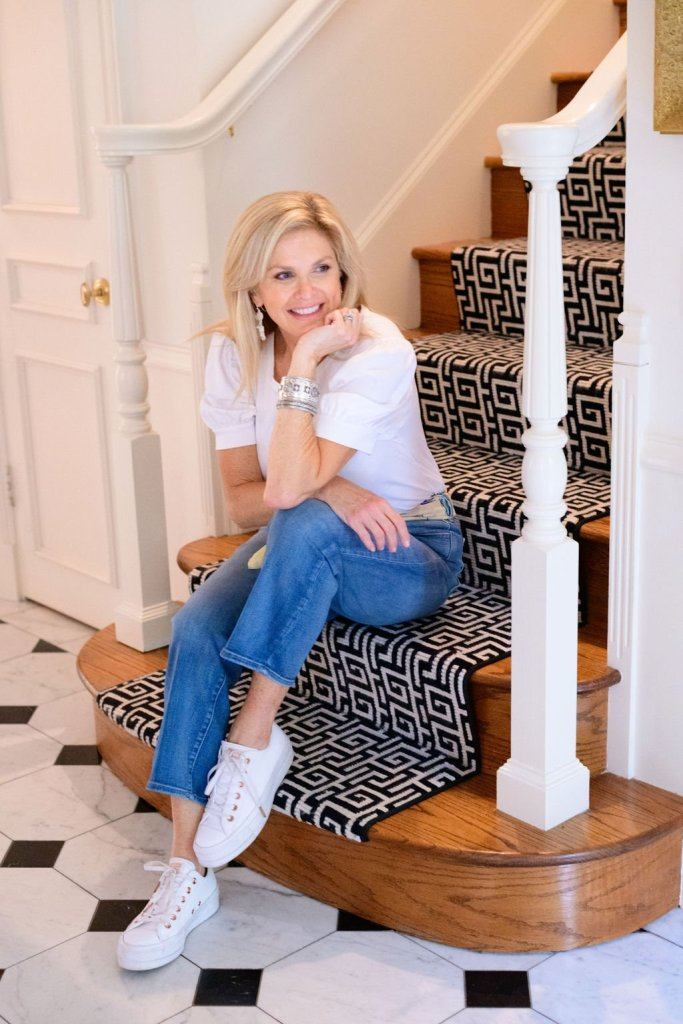Tanya Foster sitting on the stairs in chico's jeans, scarf and puff sleeve shirt with chico's earrings and bracelets and converse sneakers