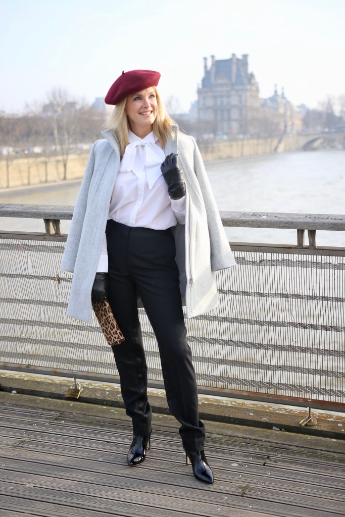 Talbots grey coat over black tuxedo pants and white blouse with a burgundy beanie on a Paris bridge overlooking the Seine river