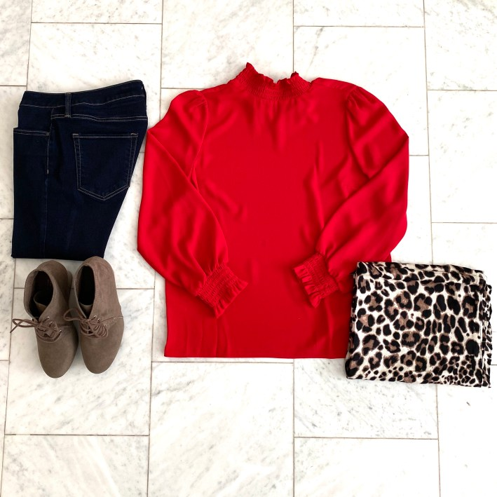 clothes flat lay featuring red blouse, booties and animal print scarf