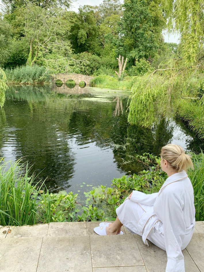 Monart Spa, Ireland | 8 Reasons to travel to Ireland now! by popular Dallas travel blogger, Tanya Foster: image of a woman sitting on some steps by a pond at the Monart Spa.