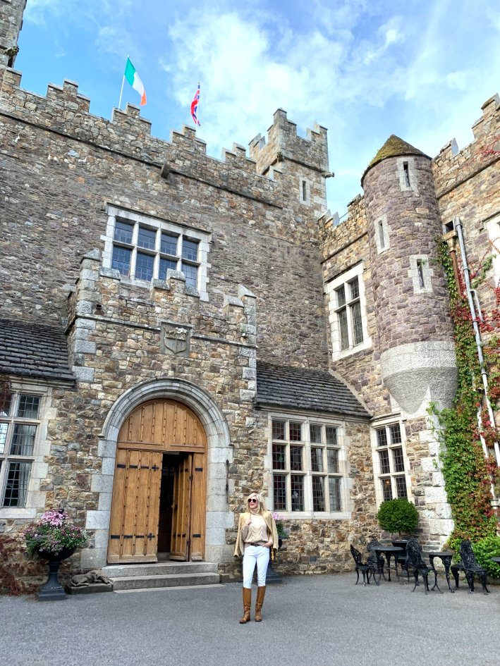 Waterford Castle in Ireland | 8 Reasons to travel to Ireland now! by popular Dallas travel blogger, Tanya Foster: image of a woman standing outside of Waterford Castle in Ireland.