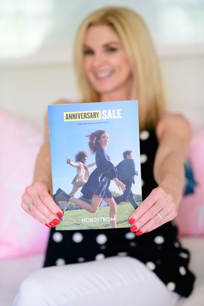 Tanya Foster holding Nordstrom Anniversary Sale catalog