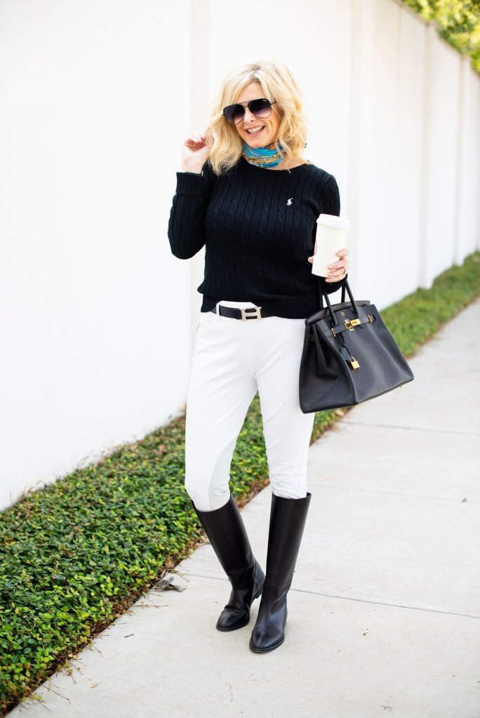5 Style Tips for a Classic Look | 5 Tips for Creating Classic Style Fashion by popular Dallas fashion blogger, Tanya Foster: image of woman standing outside and wearing a black POLO RALPH LAUREN Cable-Knit Cotton Sweater, HERMÈS Reversible H 32mm Belt Kit, Gucci silk scarf, ECP RideTex Competition Breeches White, black knee-high boots, and holding a black Prada Saffiano Cuir Double Small Tote Bag.