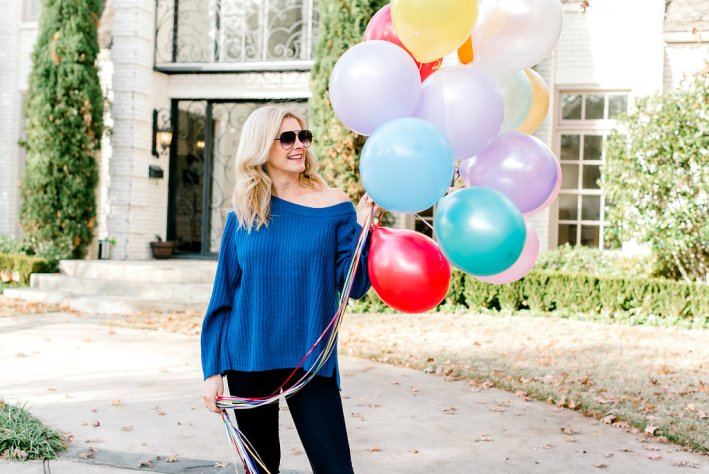 Sanctuary sweater, black pants, Taryn Rose boots with birthday balloons