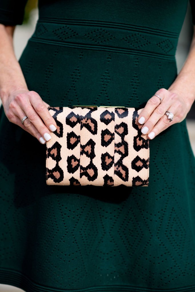 Tanya Foster holding an Officina del Poggio clutch in an Eliza J sweater dress