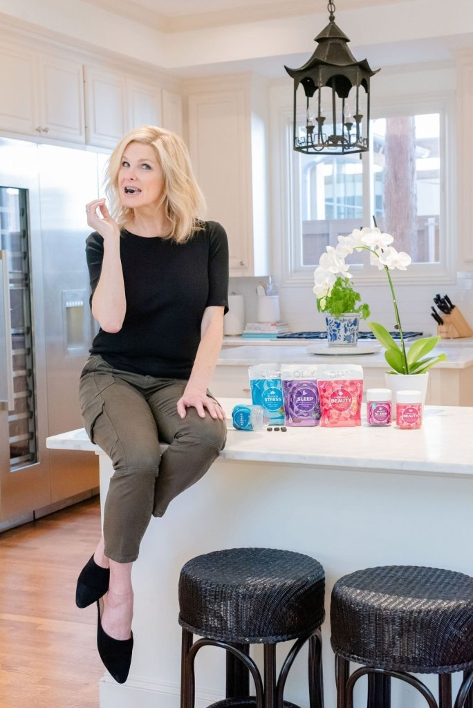 Why I love my Olly Vitamins! by popular life and style blogger, Tanya Foster: image of a woman sitting next to containers or Olly Vitamins on top of her kitchen counter and biting a vitamin between her teeth.