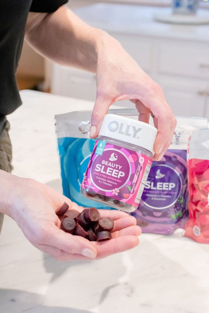 Why I love my Olly Vitamins! by popular life and style blogger, Tanya Foster: image of a woman holding a container of Olly Beauty Sleep Vitamins in one hand and holding a handful of Olly Beauty Sleep Vitamins in the other hand.
