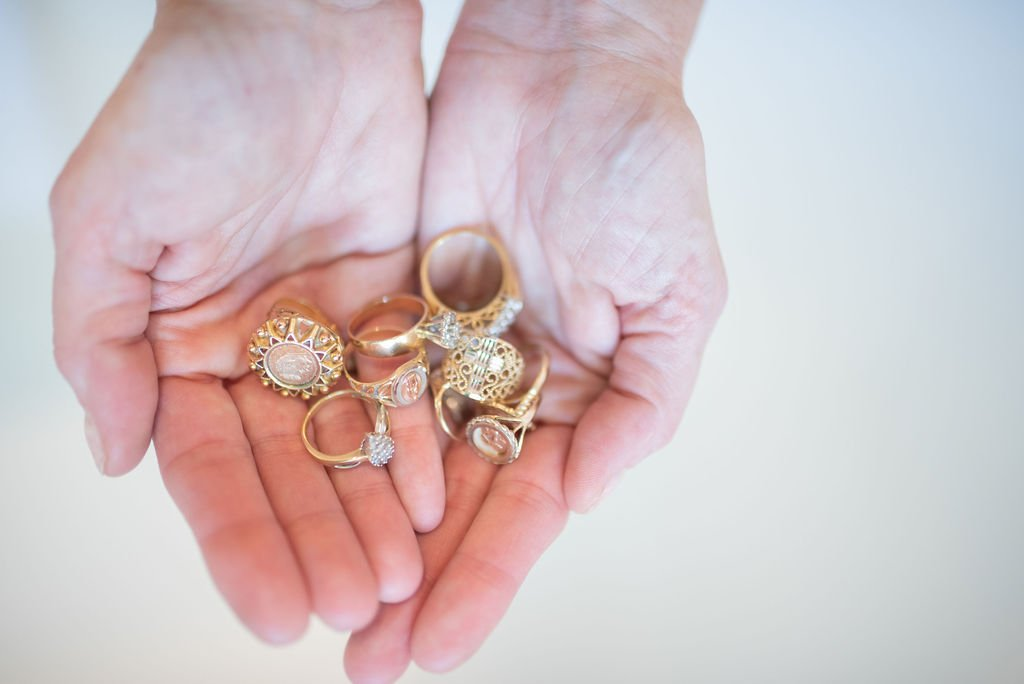 Tips on How to Move Forward After Losing a Parent by popular life and style blogger, Tanya Foster: image of two hands pressed together and holding a collection of gold rings.