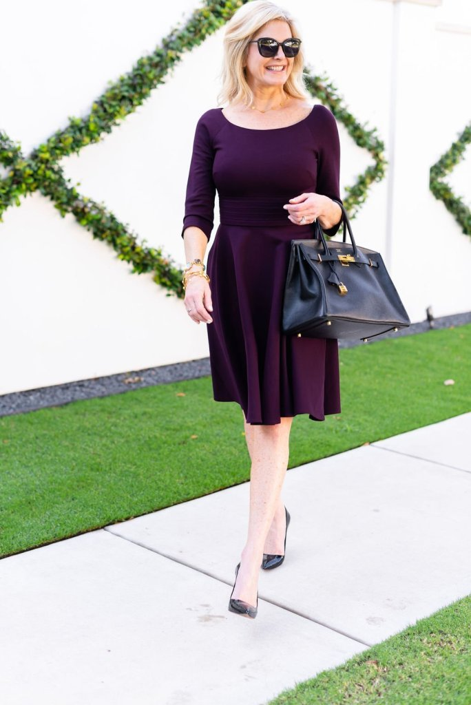 Fall color trends: an aubergine colored look featured by top US luxury fashion blogger, Tanya Foster: image of a woman wearing an Yves Saint Laurent medium sac de jour, Harper Rose fit and flare aubergine dress, Sam Edelman toe pumps, Yves Saint Laurent round sunglasses, David Yurman chain bracelet and Kate Spade bangles.