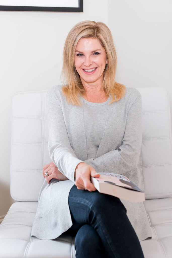 Tanya Foster sitting and holding a book ready to be a homebody