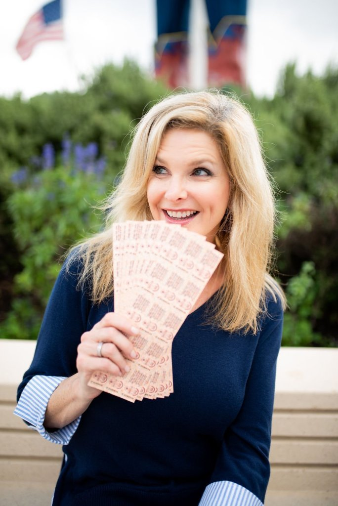 10 Things to do at the Texas State Fair! by popular Dallas blogger, Tanya Foster: image of a woman at the Texas State Fair holding some tickets.