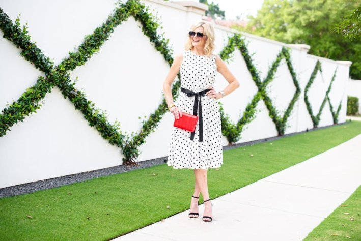 Twirling into Fall in Harper Rose midi dress |3 Things to Look for in a Polka Dot Midi Dress by popular Dallas fashion blogger, Tanya Foster: image of a woman standing outside by a white wall and wearing a Nordstrom Harper Rose Polka Dot Fit & Flare Dress, black stiletto heel sandals, sunglasses, and holding a red clutch.
