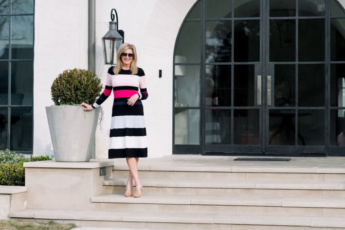 Tanya Foster standing on steps in a striped Eliza J sweater dress