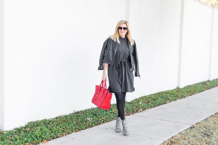 Tanya Foster standing on a sidewalk wearing a wrap dress, booties and moto jacket