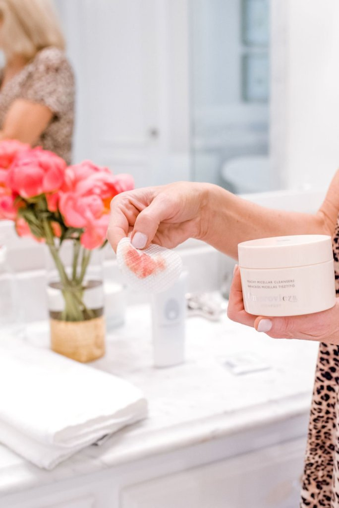 Top Benefits of Double Cleansing Your Face featured by top US beauty blogger, Tanya Foster: image of a woman holding Omorovicza's beauty products.