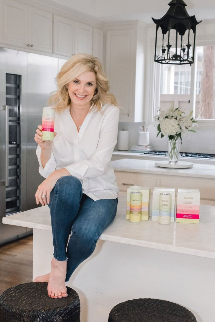 SkinTe - The Secret to Radiant Skin | The Resolution to Radiant Skin - SkinTē by popular Dallas luxury beauty blogger, Tanya Foster: image of a woman sitting on her counter and holding a SkinTe product.