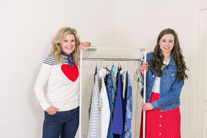 Tanya Foster and assistant standing in Talbots clothes with a rack of clothes to prep for a photoshoot