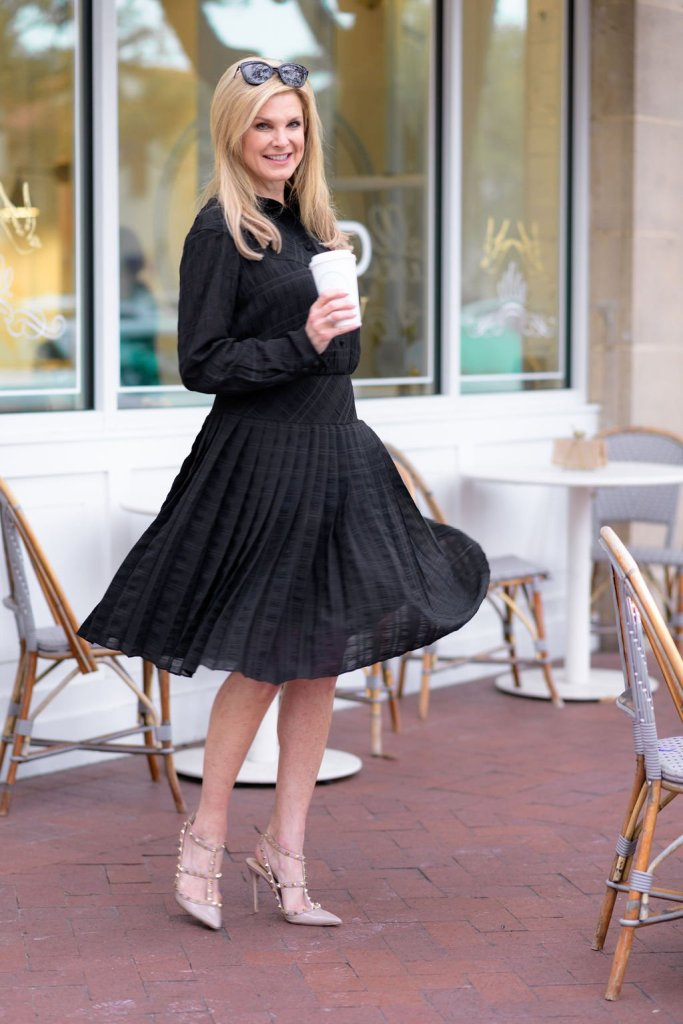 Tanya Foster spinning in a Coach black dress and Valentino heels while holding a coffee