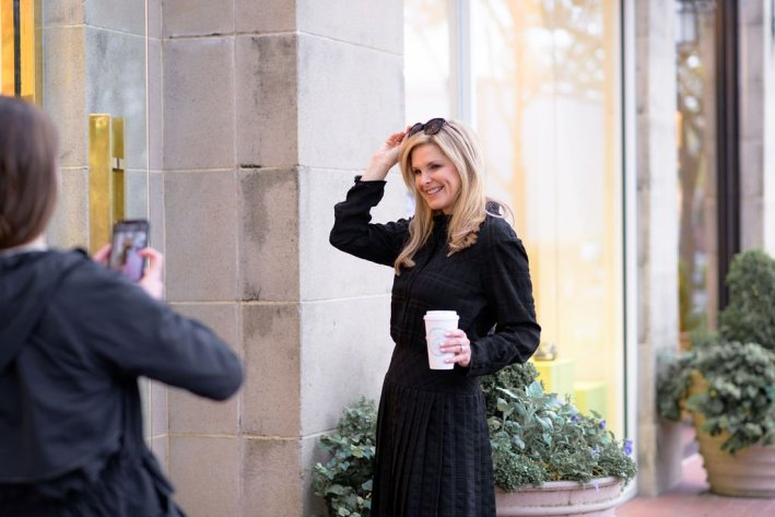 Tanya Foster in a coach spring 2020 collection black dress and sunglasses holding coffee and posing for a picture