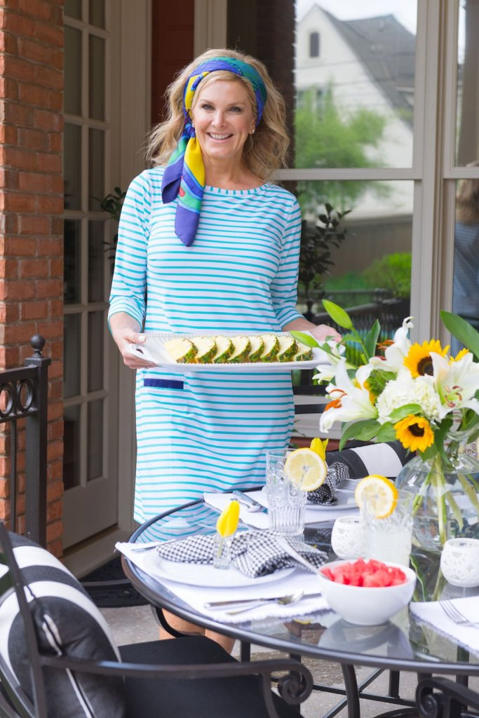 Tanya Foster holding a vietri platter with pineapple while wearing a cabana life dress