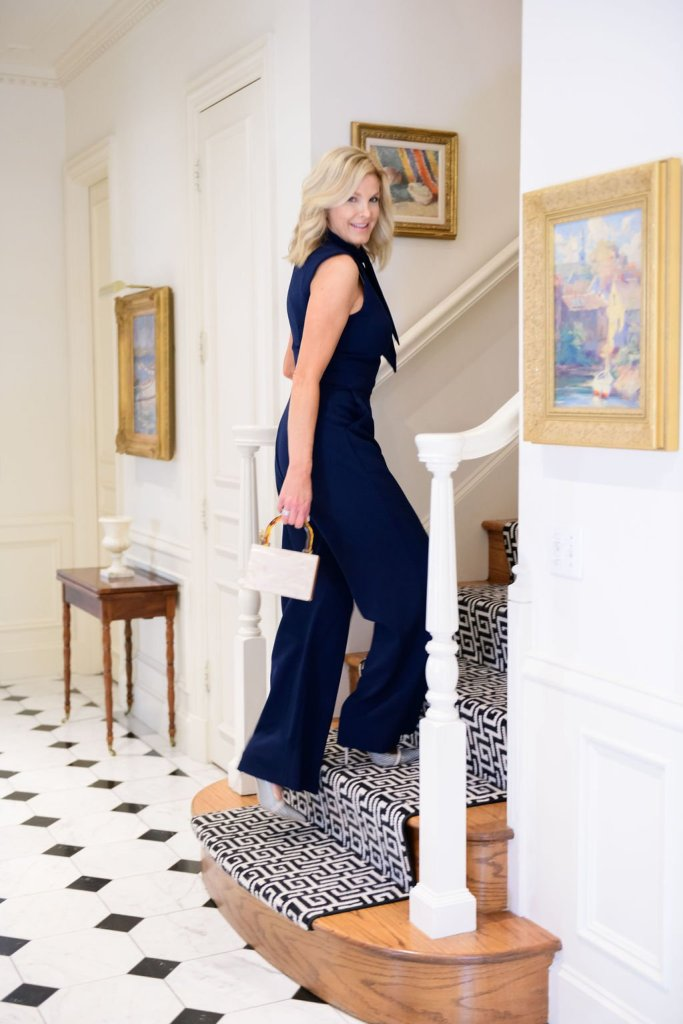 Tanya Foster walking up the stairs in Harper Rose navy scarf neck crepe jumpsuit