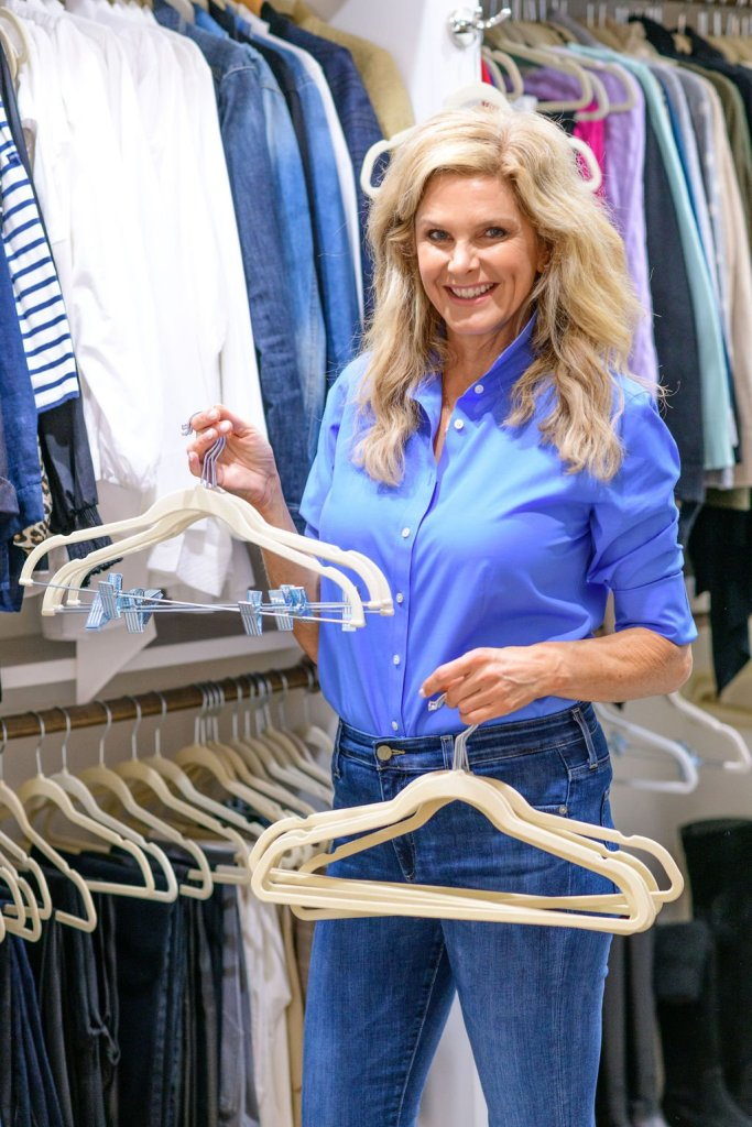 Tanya Foster in blue talbots blouse and jeans holding hangers