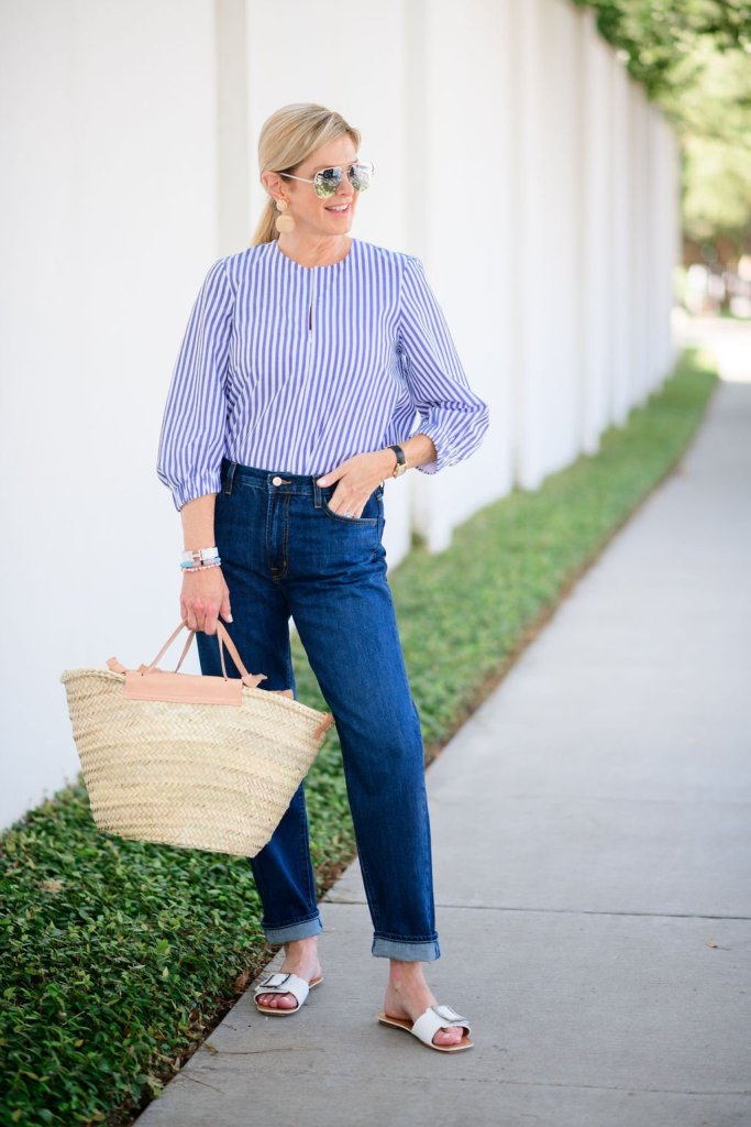 Tanya Foster in j brand dark wash boyfriend jeans and a tuckernuck blouse and tuckernuck earrings with a mango straw tote bag