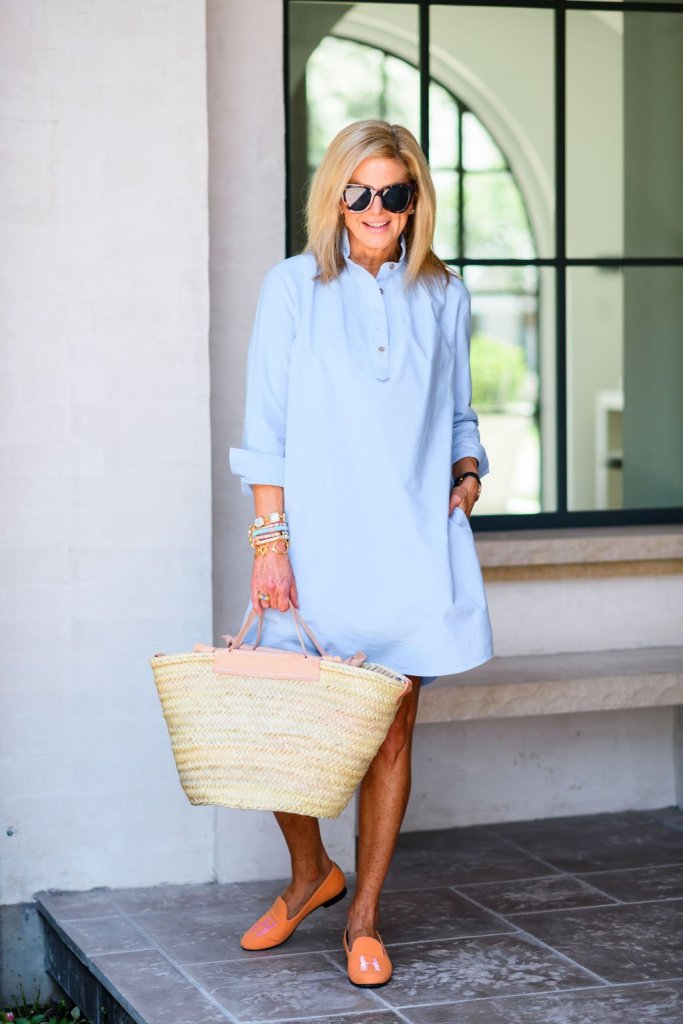 Tanya Foster wearing tuckernuck blue chambray shirt dress with hadleighs orange loafer slippers and a mango straw bag