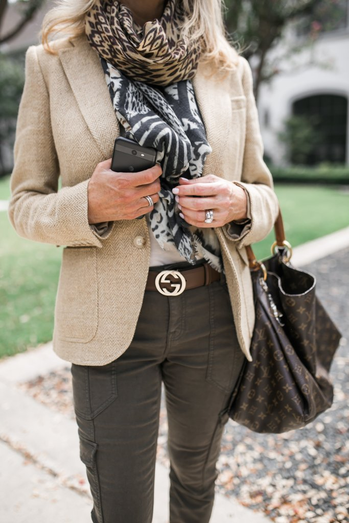 Tanya Foster in a blazer and army green pants with a louis vuitton bag and gucci belt