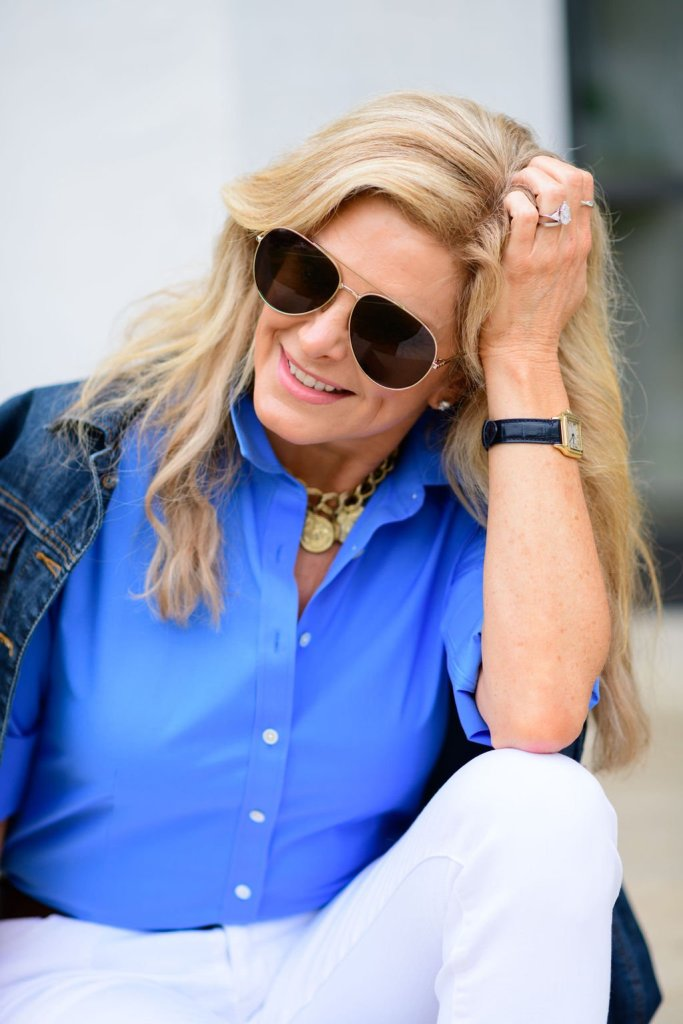 Tanya Foster sitting in white jeans talbots blue button up blouse and jean jacket with nest jewelry