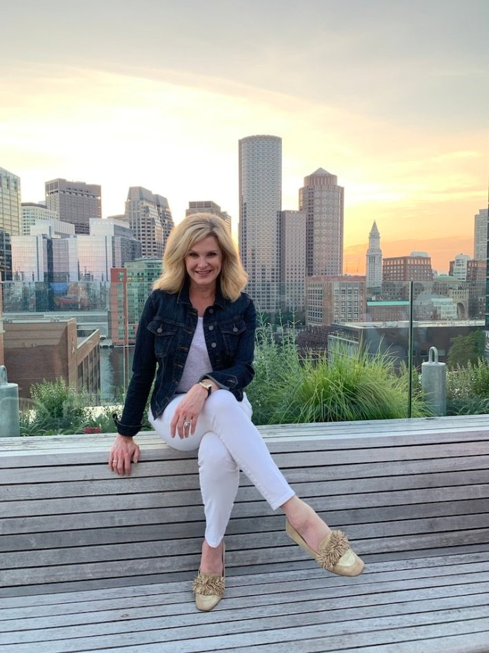 Tanya Foster visits Boston and shares her recommendations | Destination: Boston, Massachusetts Travel Guide by popular Dallas travel blogger, Tanya Foster: image of a woman sitting on a wooden bench with the Boston skyline behind her.