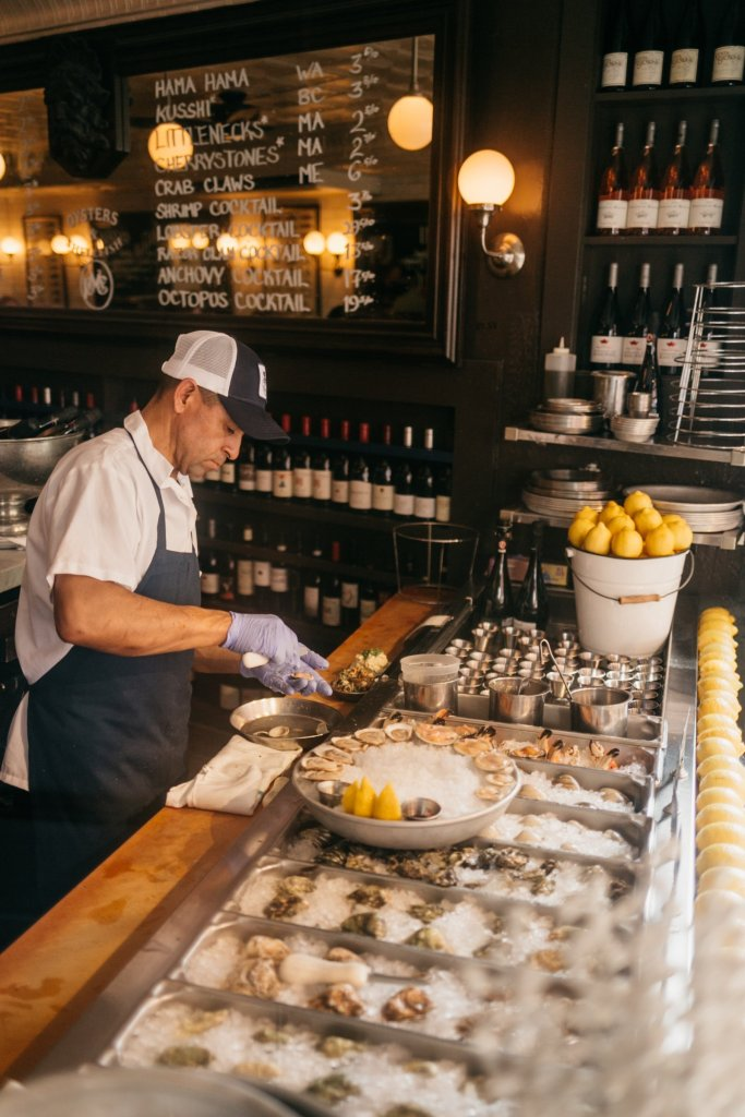 Tanya Foster visits Boston and shares her recommendations | Destination: Boston, Massachusetts Travel Guide by popular Dallas travel blogger, Tanya Foster: image of a man shucking oysters.