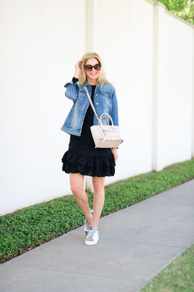 Tanya Foster wearing avara black dress with a jean jacket and sneakers
