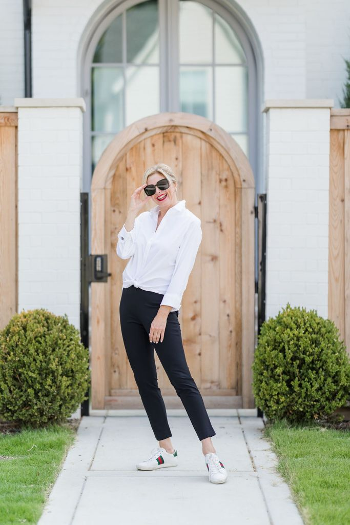 Tanya foster wearing chico's white button up blouse and black chino pants with gucci sneakers