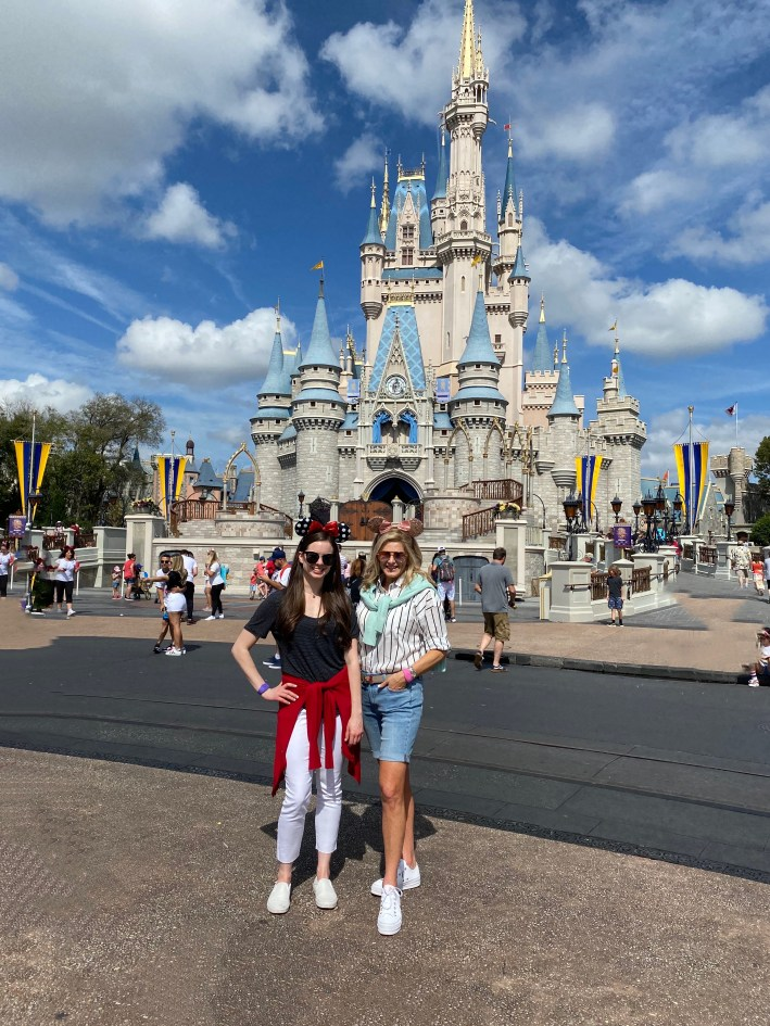Tanya Foster and assistant standing in front of Disney World's magic kingdom castle