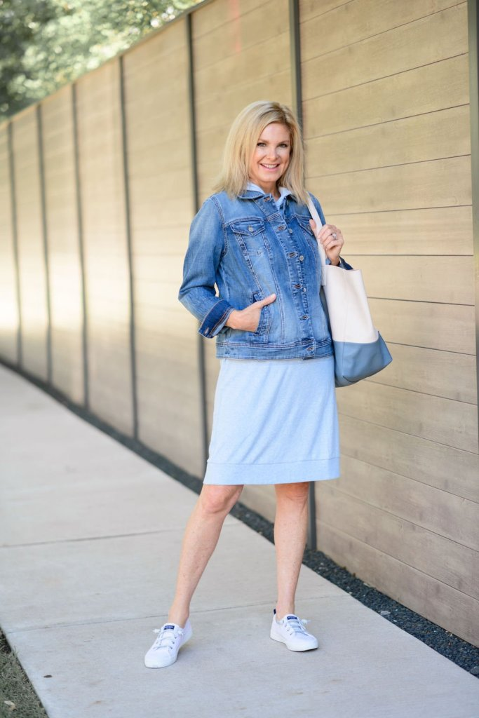 Tanya foster in chico's dress and denim jacket with a bag and sneakers