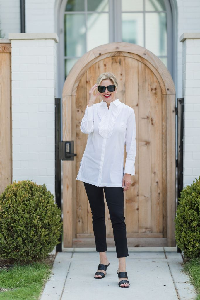 Tanya foster wearing chico's white blouse and black chino pants with vince camuto slide sandals