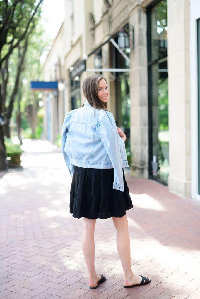 Woman wearing avara black dress and jean jacket