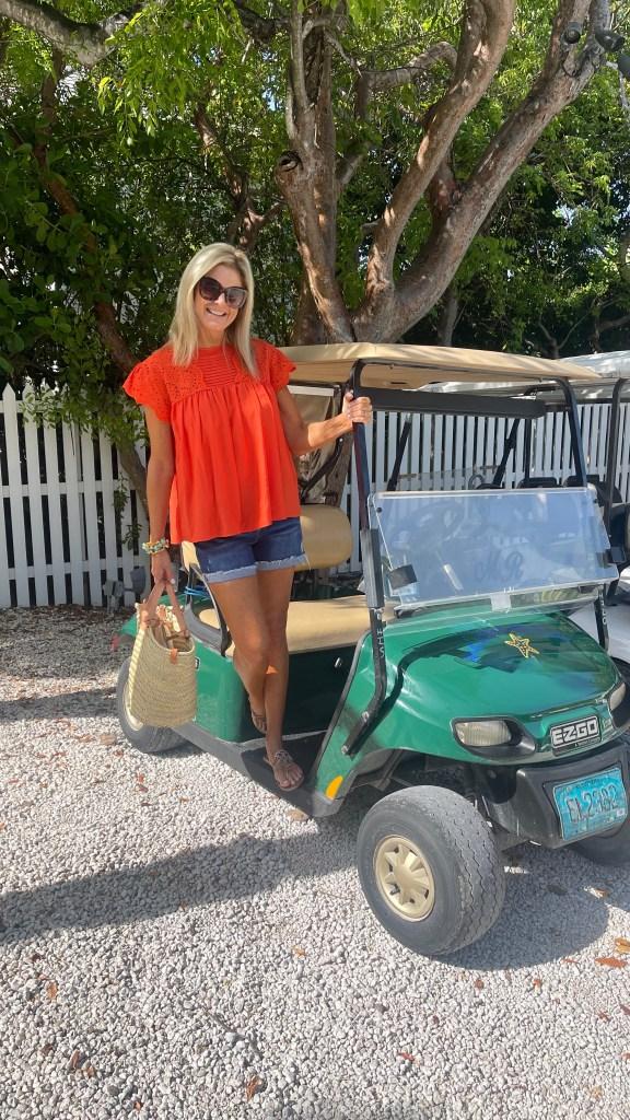 Tanya Foster on a golf cart wearing Avara orange top and denim shorts