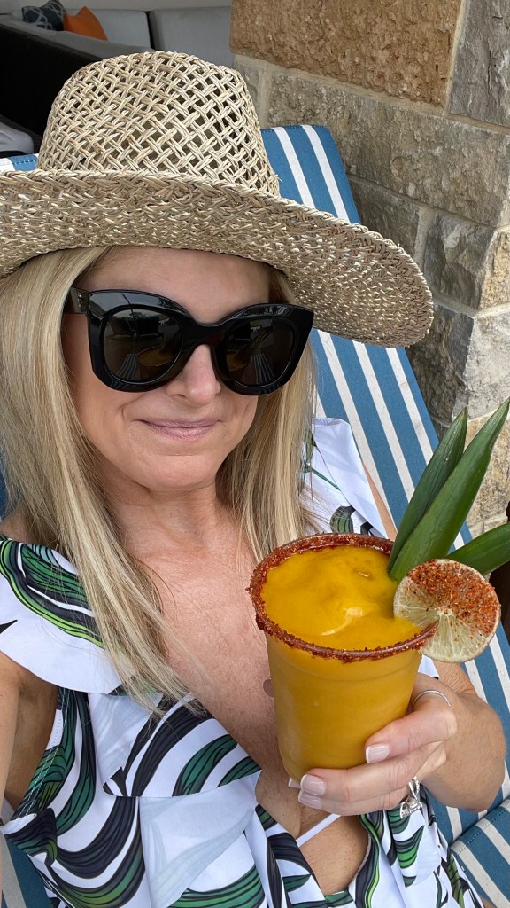 tanya foster wearing lounging in swimsuit with a drink