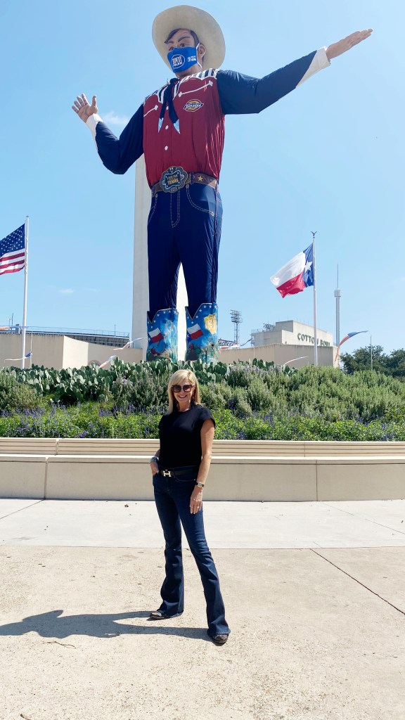tanya foster standing in front of big tex in in frame denim and black tee